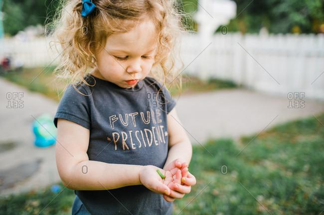 Little girl holding green caterpillar