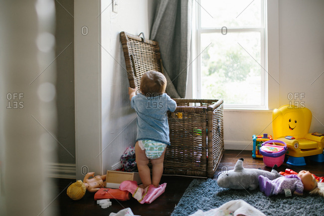 Baby standing by toy box