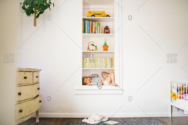 Little girl lying in nook on bookshelf