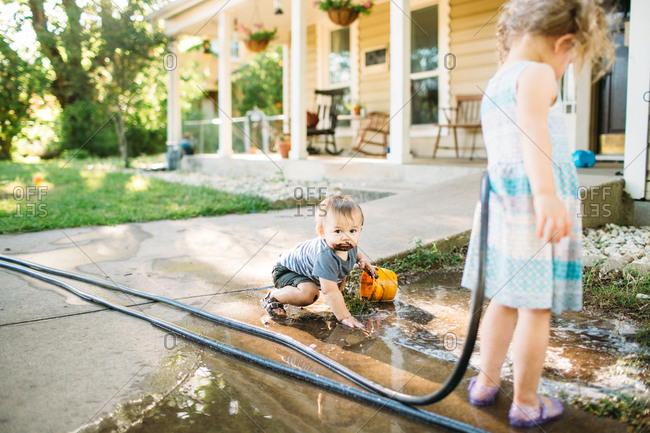Two kids playing with hose and muddy puddles