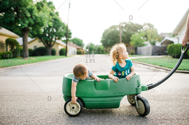 Two kids riding in a green wagon