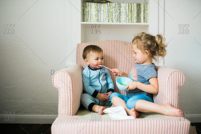 Big sister feeding little brother