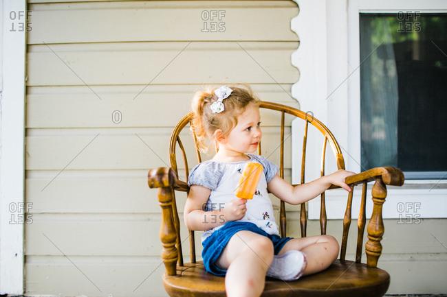 Little girl eating an orange popsicle