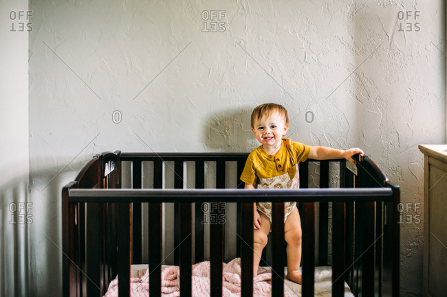 Happy baby boy standing in a crib