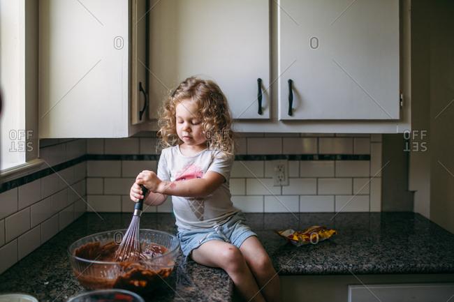 Little girl stirring cake batter on kitchen counter