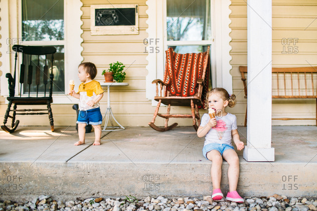 Siblings sitting on a porch eating ice cream cones