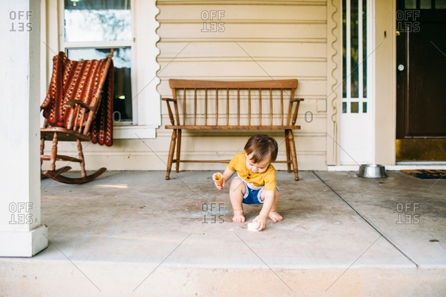 Toddler picking up ice cream he dropped on a porch