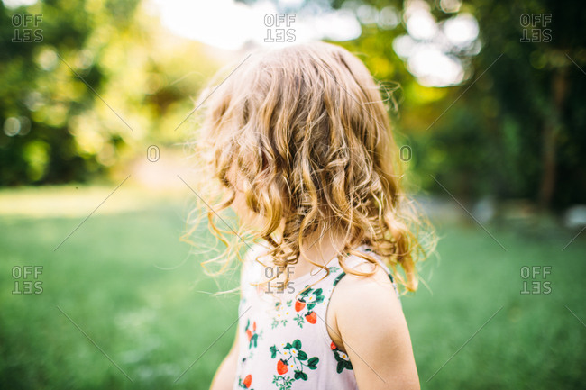 Blonde toddler with curly hair looking away