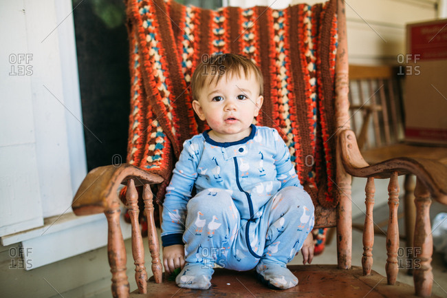 Baby boy sitting in rocking chair on porch