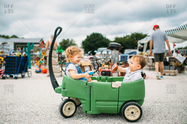 Two little kids riding in a green wagon