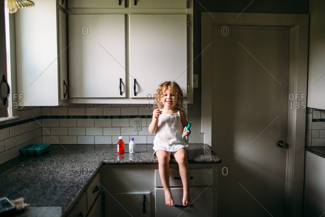 Toddler girl sitting on counter taking medicine