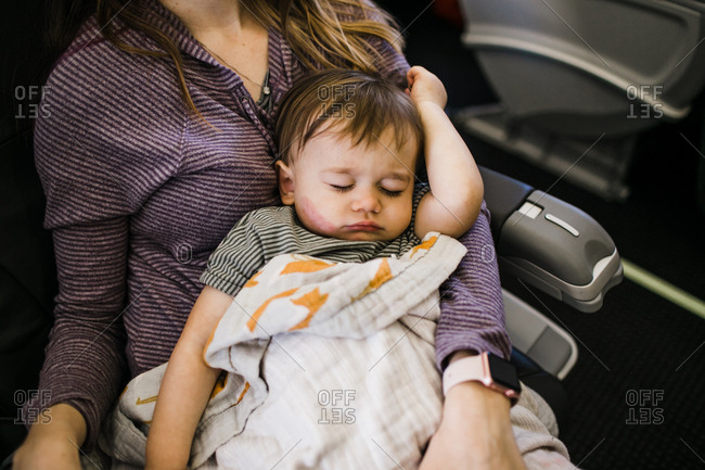 Baby sleeping in woman's lap on an airplane