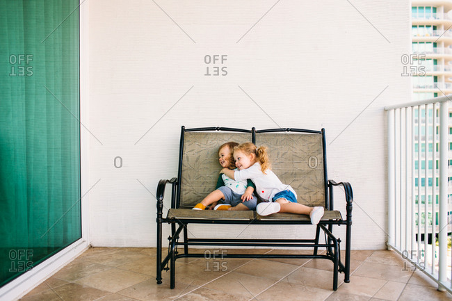 Two kids sitting on a patio seat hugging