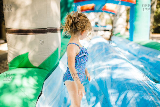 Toddler playing on inflatable water slide