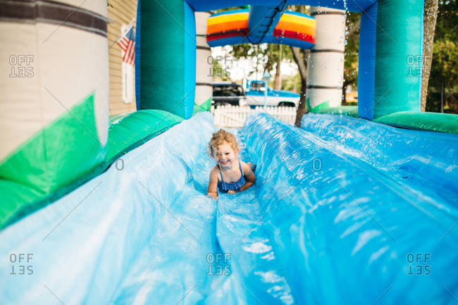 Toddler sliding on inflatable water slide