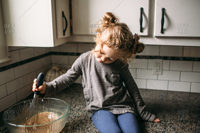 Little girl stirring batter on kitchen counter