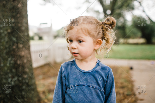 Little girl with blonde curly hair outdoors