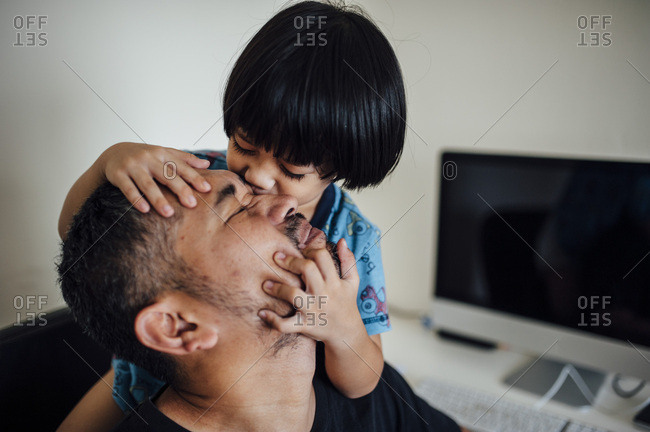 Little boy kissing father's face
