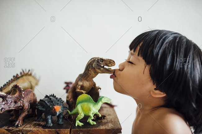 Young boy kissing toy dinosaur