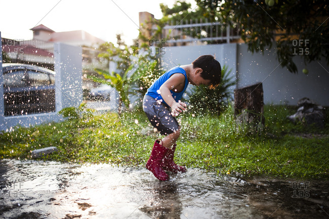 Boy jumping in puddle with rubber boots