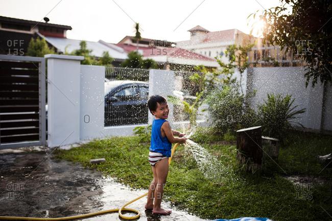 Boy spraying water hose in backyard