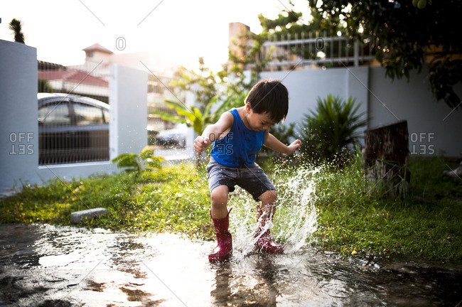 Boy splashing in puddle with rubber boots