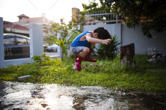 Boy hopping in puddle with rubber boots