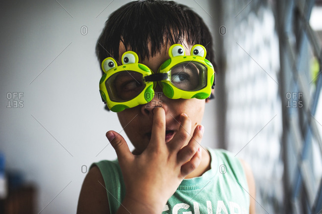 Young boy wearing goggles and picking his nose