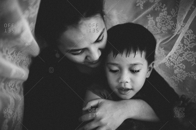 Mother lying with arms around her son