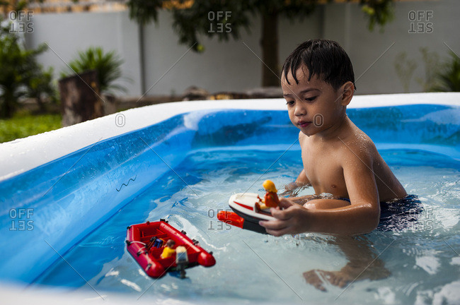 Boy swimming in backyard pool