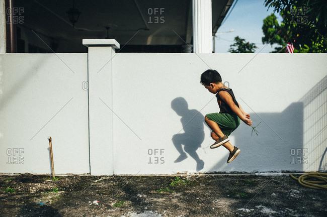 Boy looking at his shadow while jumping
