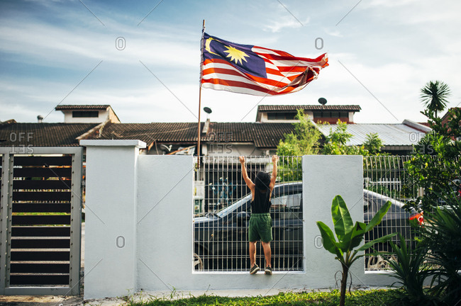 Boy climbing fence by Malaysian flag