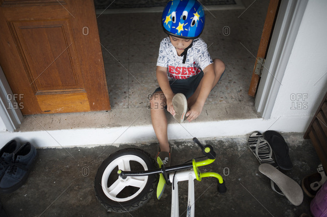 Boy putting shoes on before riding bike