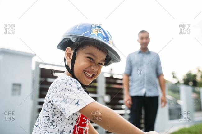 Father watching son ride bike