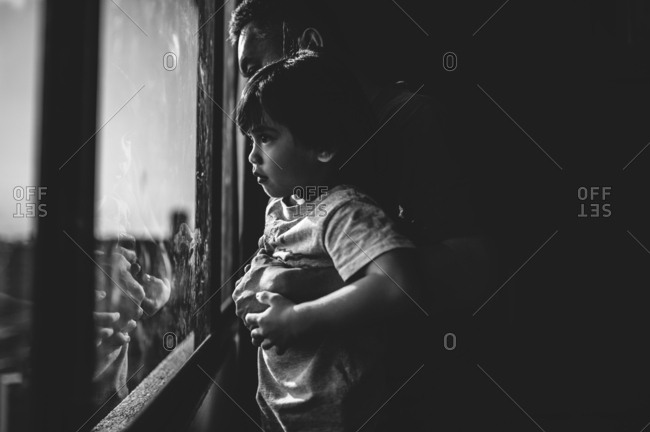 Man lifting his son to look out a window