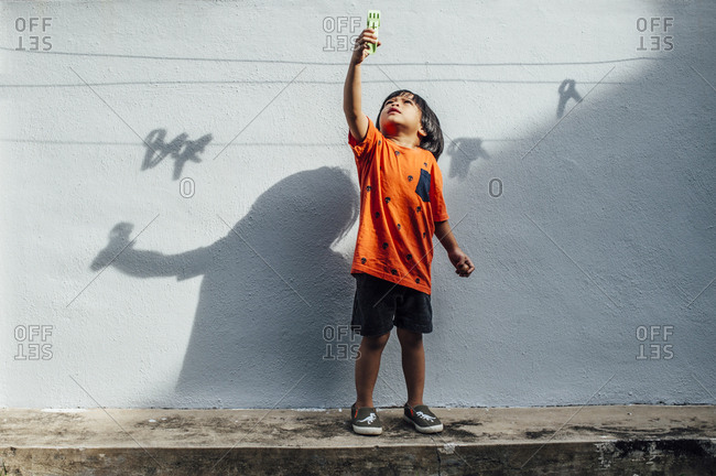 Boy holding toy up in the air
