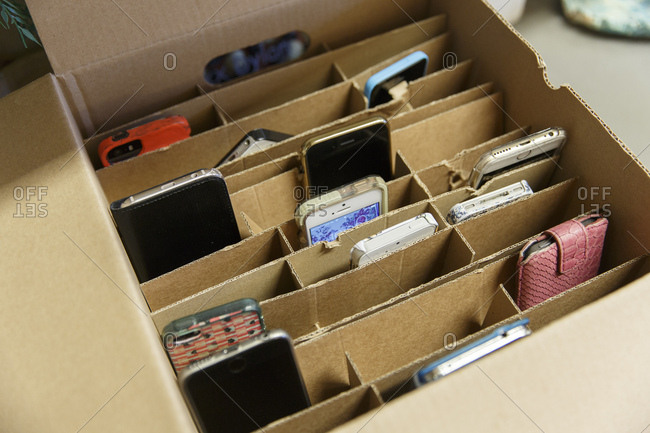 Netherlands - September 21, 2017: Smartphones owned by school kids in a box, stored by the teacher during class in a high school