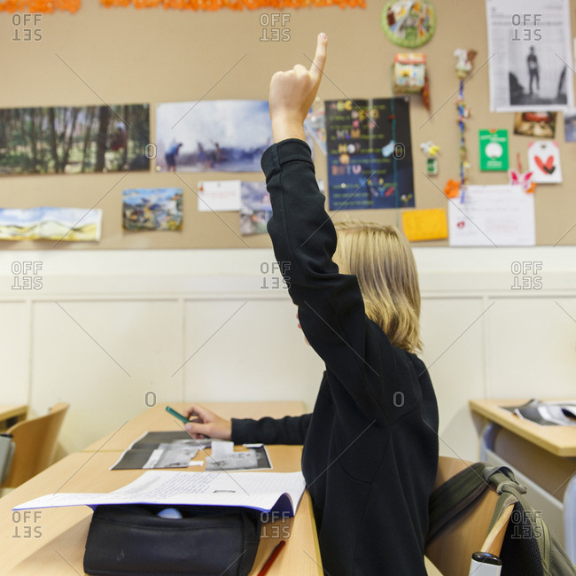 Boy raising his finger to ask or answer a question during class in a high school in the Netherlands