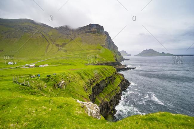 Vagar, Faroe islands, Denmark - June 14, 2017: Huge cliffs in Gasadalur