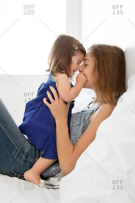 Mother holding her daughter while rubbing noses together