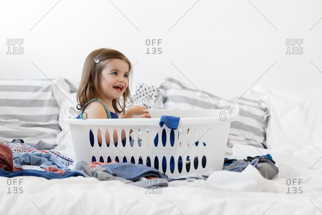 Toddler girl sitting in empty laundry basket surrounded by clothes