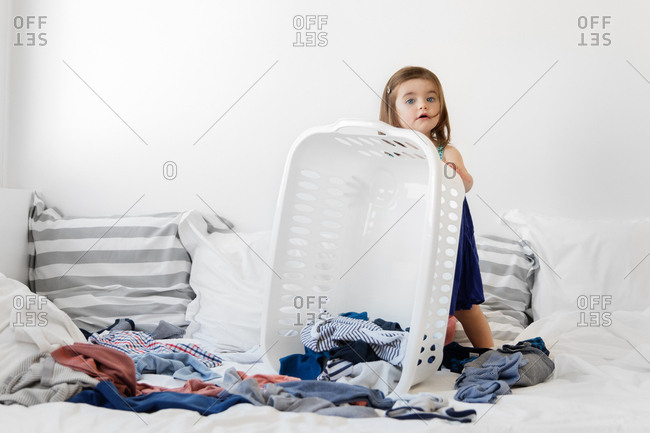 Toddler girl emptying clothes from laundry basket onto bed