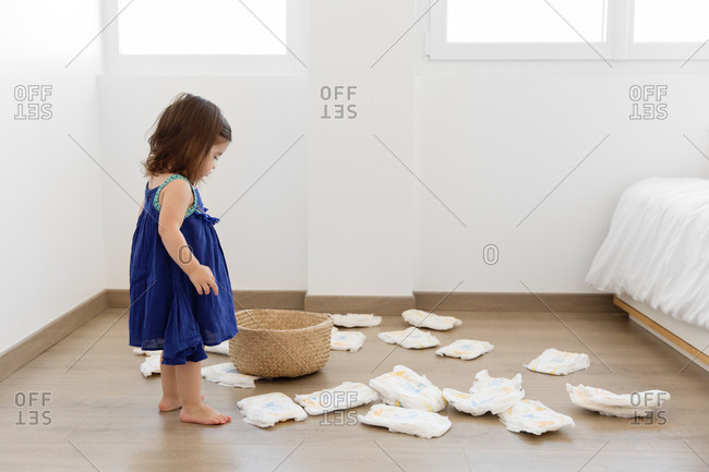 Little girl looking at many diapers and empty basket on floor