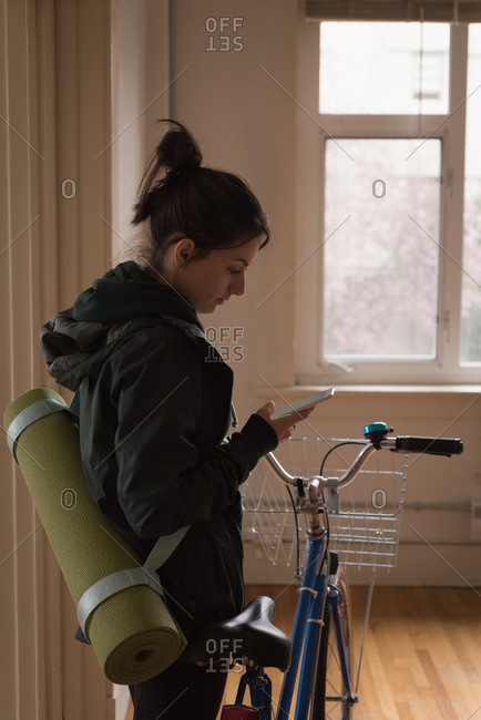 Side view of young woman with bicycle using phone at home