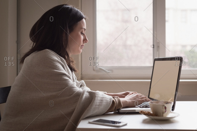 Young woman using laptop on table at home