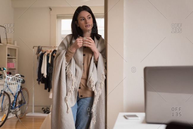 Thoughtful young woman with coffee cup standing at home