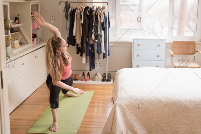 Full length of young woman exercising in bedroom at home