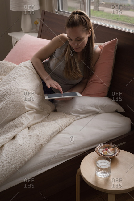 Young woman using tablet on bed at home