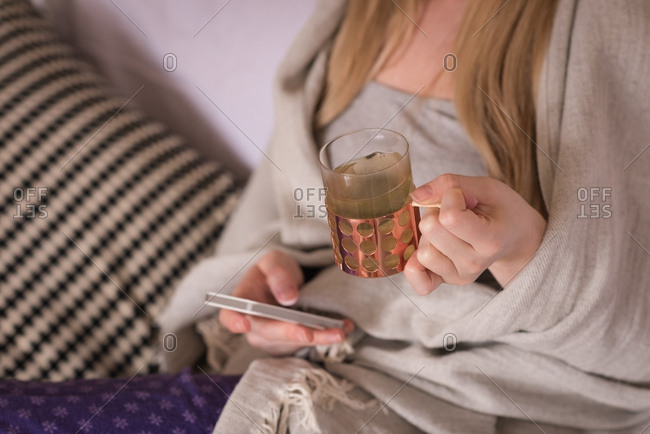 Mid section of woman with drink using mobile phone on sofa at home