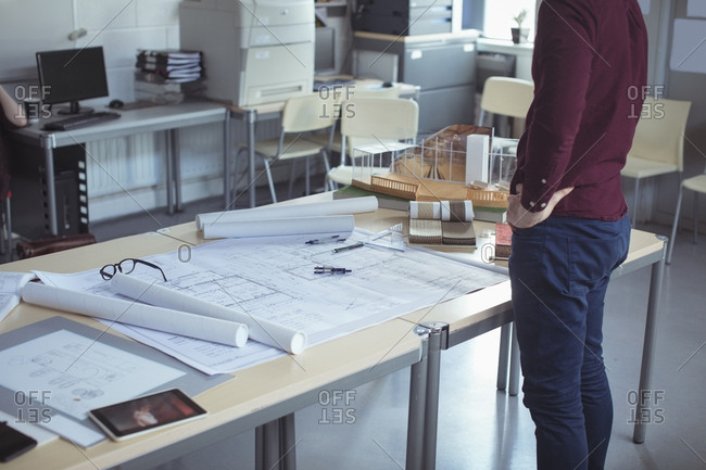 Mid section of architect standing with hands on hip at table in studio